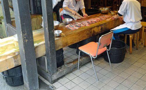 川豊の店先で手際よくうなぎをさばく職人